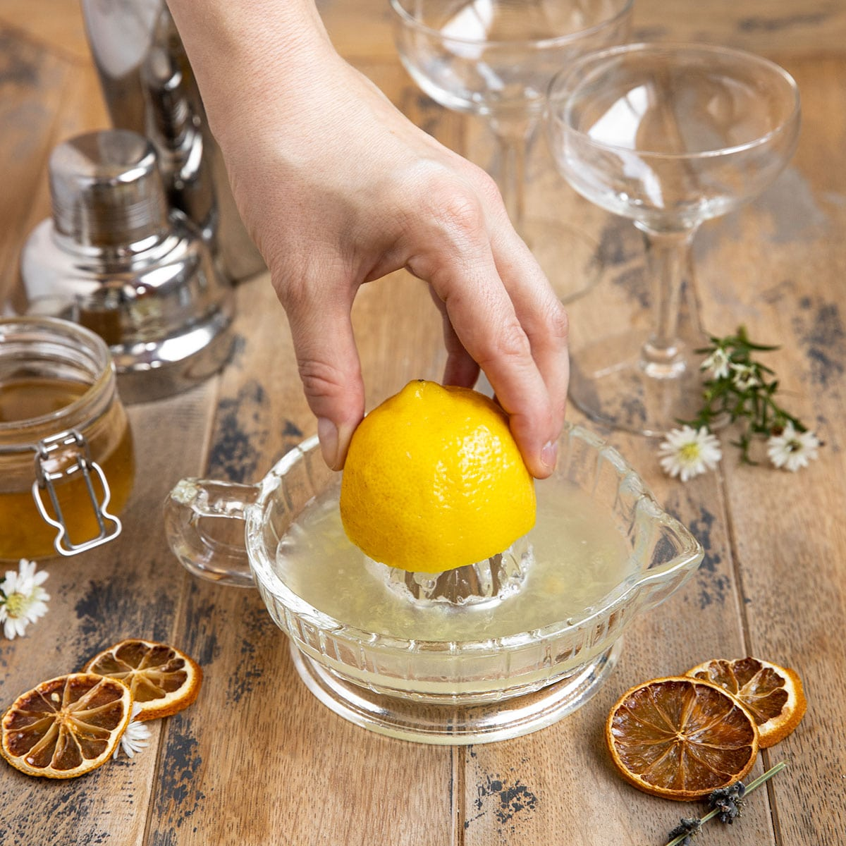 juicing a lemon in a glass citrus reamer