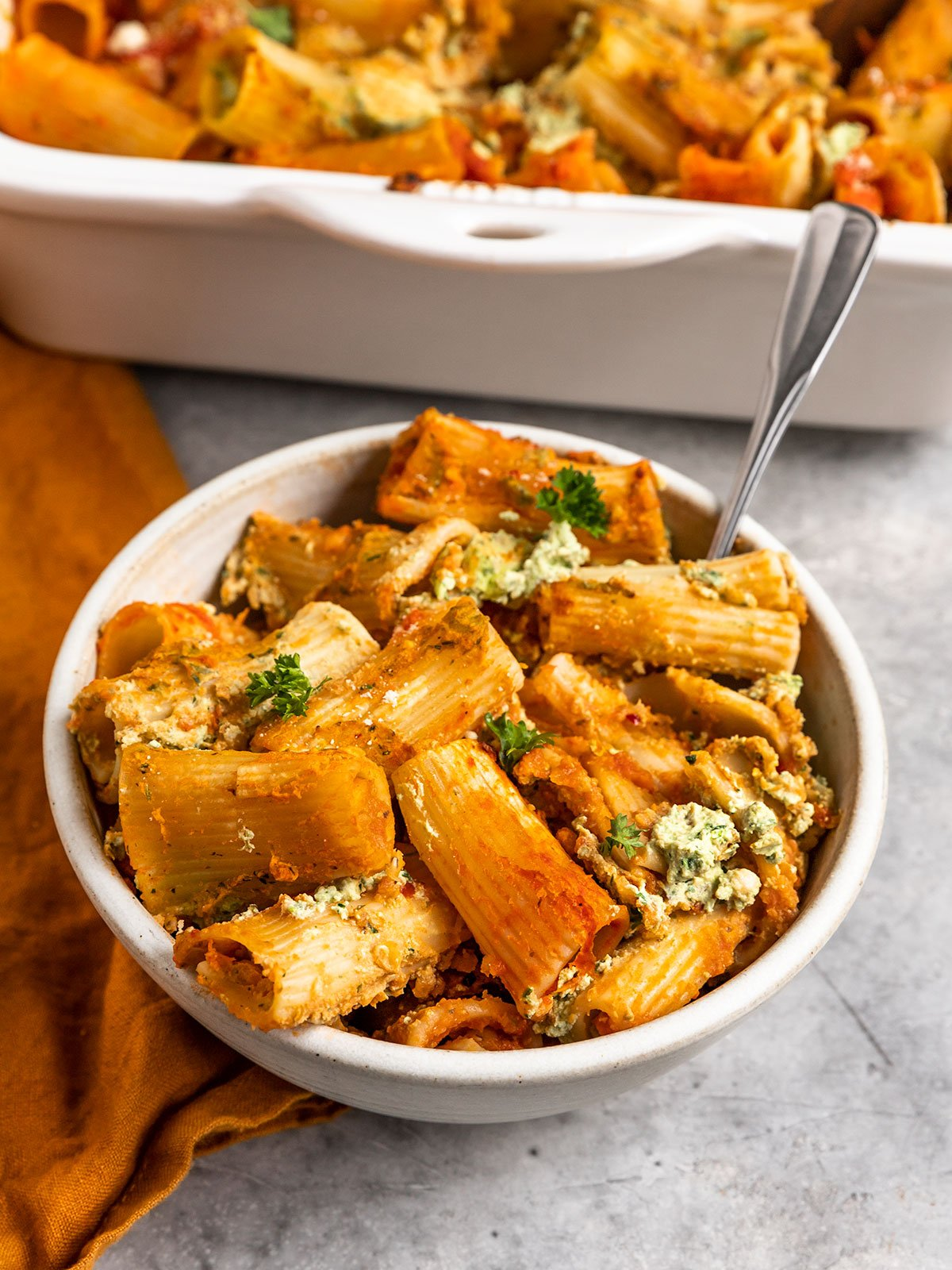 a bowl of pasta with tomato sauce, lentils, tofu ricotta, and parsley