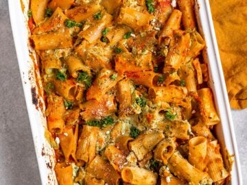 a big pan of ziti with tofu ricotta, tomato sauce, and lentils with parsley on top