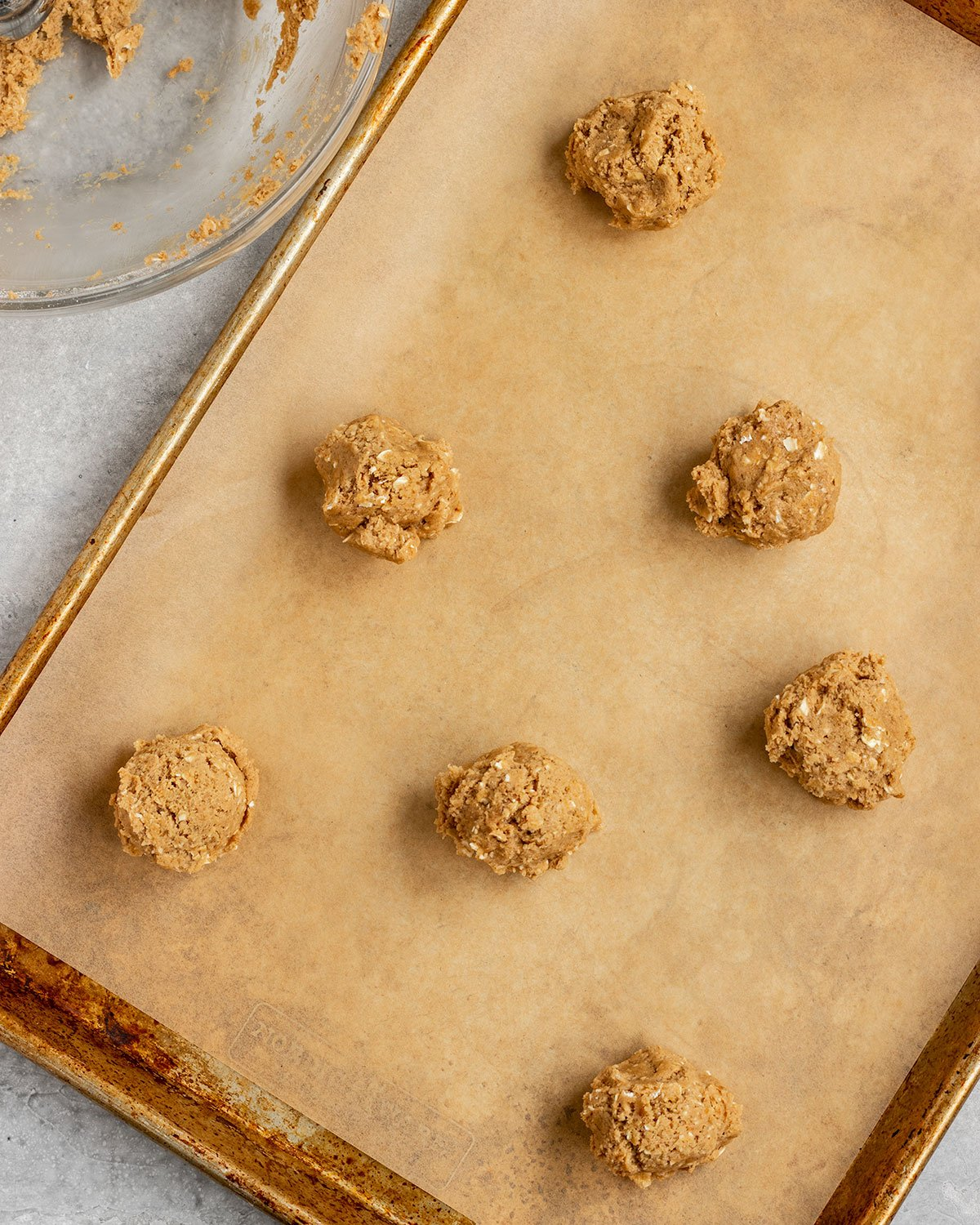 overhead shot of oatmeal cookie dough balls on a parchment lined baking sheet