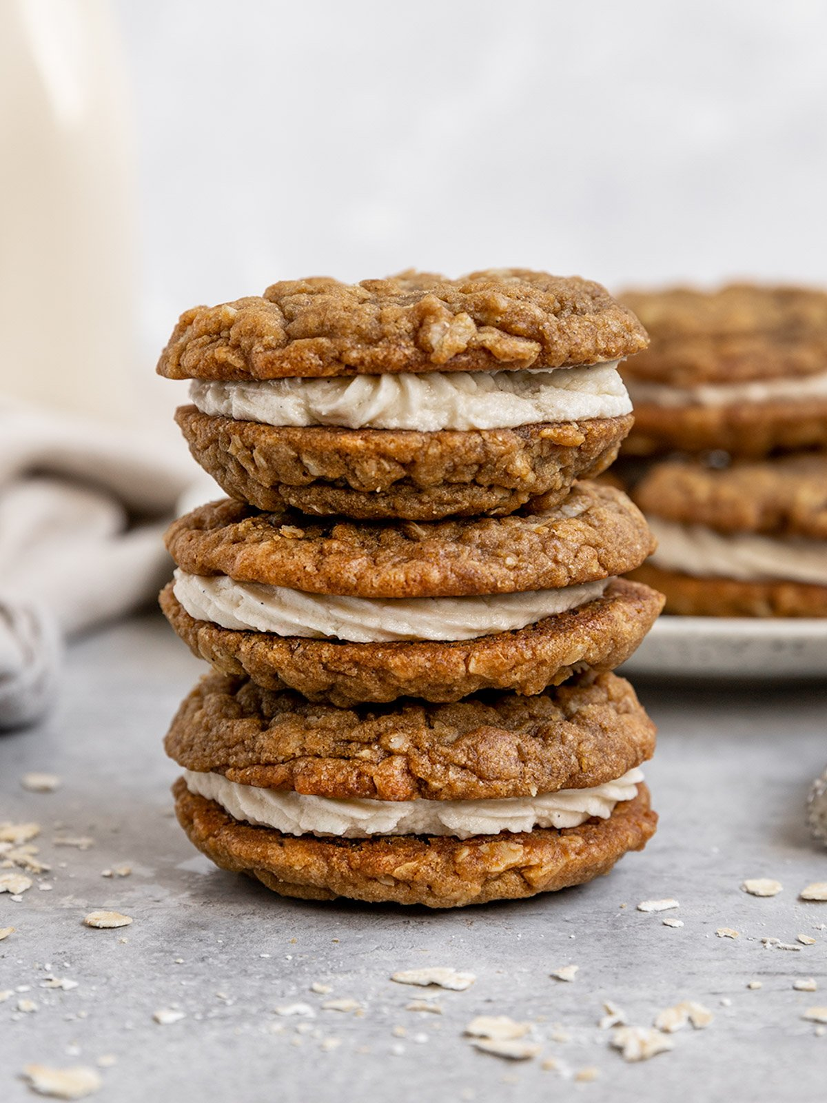 three oatmeal cookies filled with frosting stacked on top of each other beside milk and a plate of more cookies
