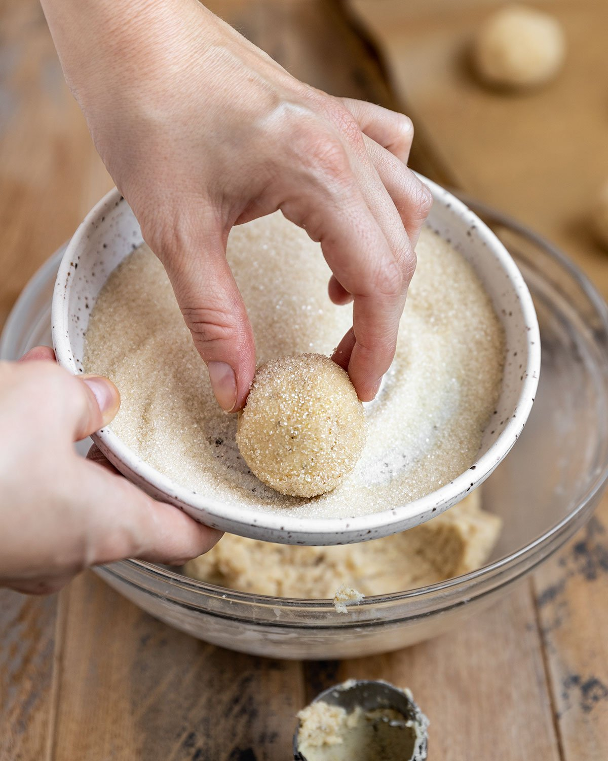 hand rolling a chamomile cookie dough ball in a bowl of sugar until it is coated