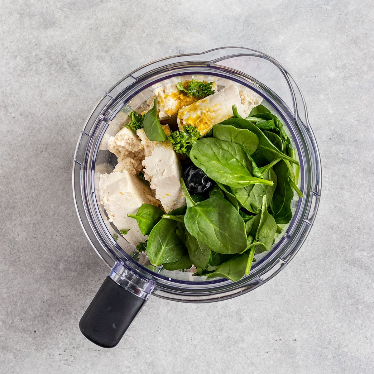ingredients in blender including spinach, tofu, nutritional yeast, spices, and lemon juice