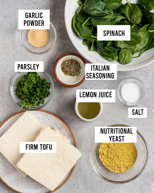 overhead shot of labeled ingredients for tofu ricotta including spinach, firm tofu, nutritional yeast, garlic powder, Italian seasoning, salt, lemon juice, and parsley