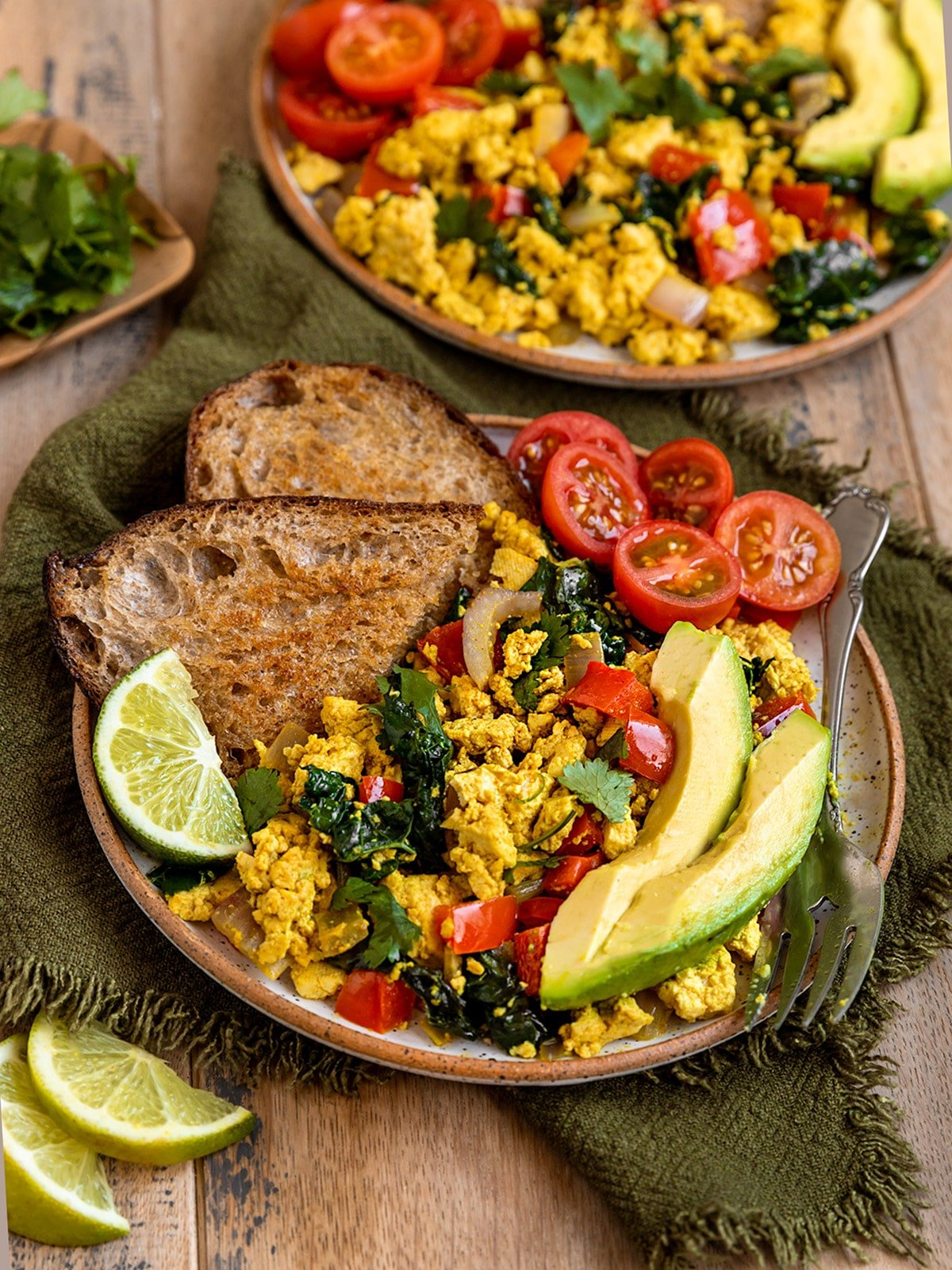 two plates topped with a tofu scramble, vegetables, avocado, cherry tomatoes, toast, and a lime wedge