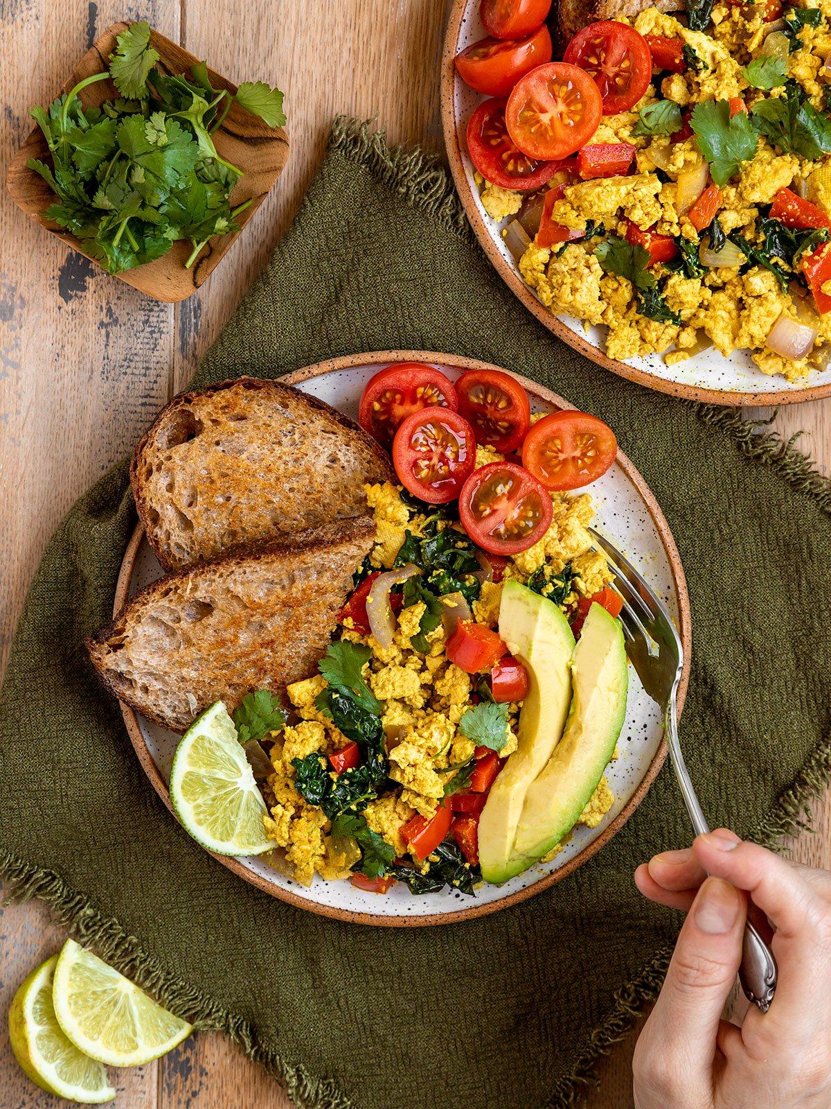 overhead shot of hand digging into plate of scrambled tofu, avocado, tomatoes, and toast