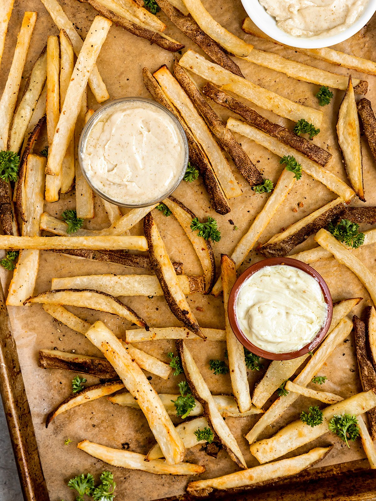 overhead shot of tray of baked fries with truffle and parsley with two bowls of mayo