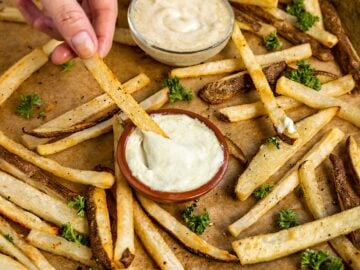 hand dipping a baked fry into a small bowl of vegan mayo
