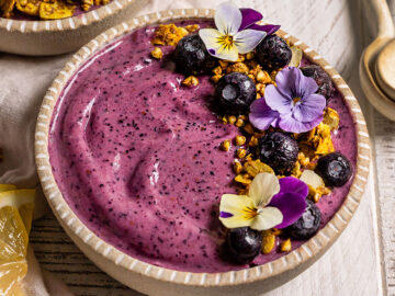 a purple smoothie bowl with blueberries, granola, and pansy flowers on top