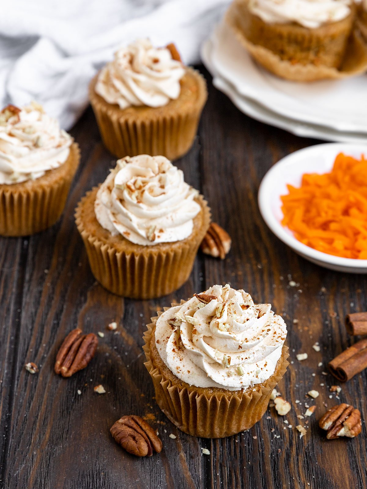 five carrot cake cupcakes on a wooden board with maple frosting and chopped pecans on top