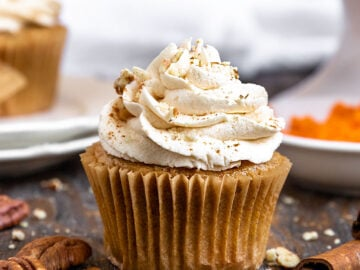 a close up shot of a carrot cake cupcake with maple frosting and pecans crumbled on top
