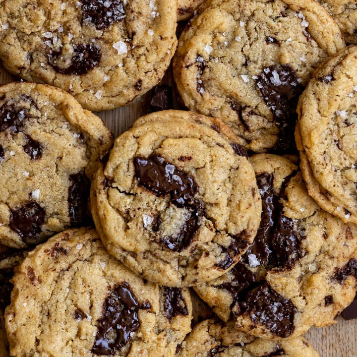 overhead shot of chocolate chip cookies piled on top of each other with flaky sea salt on top