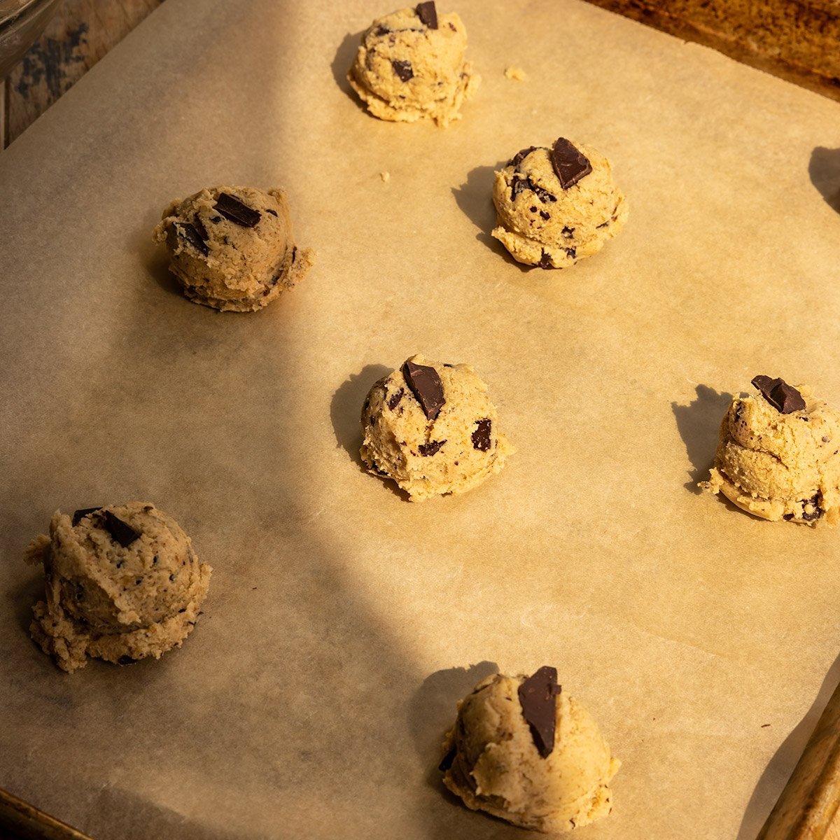 parchment lined baking sheet topped with chocolate chip cookie dough balls