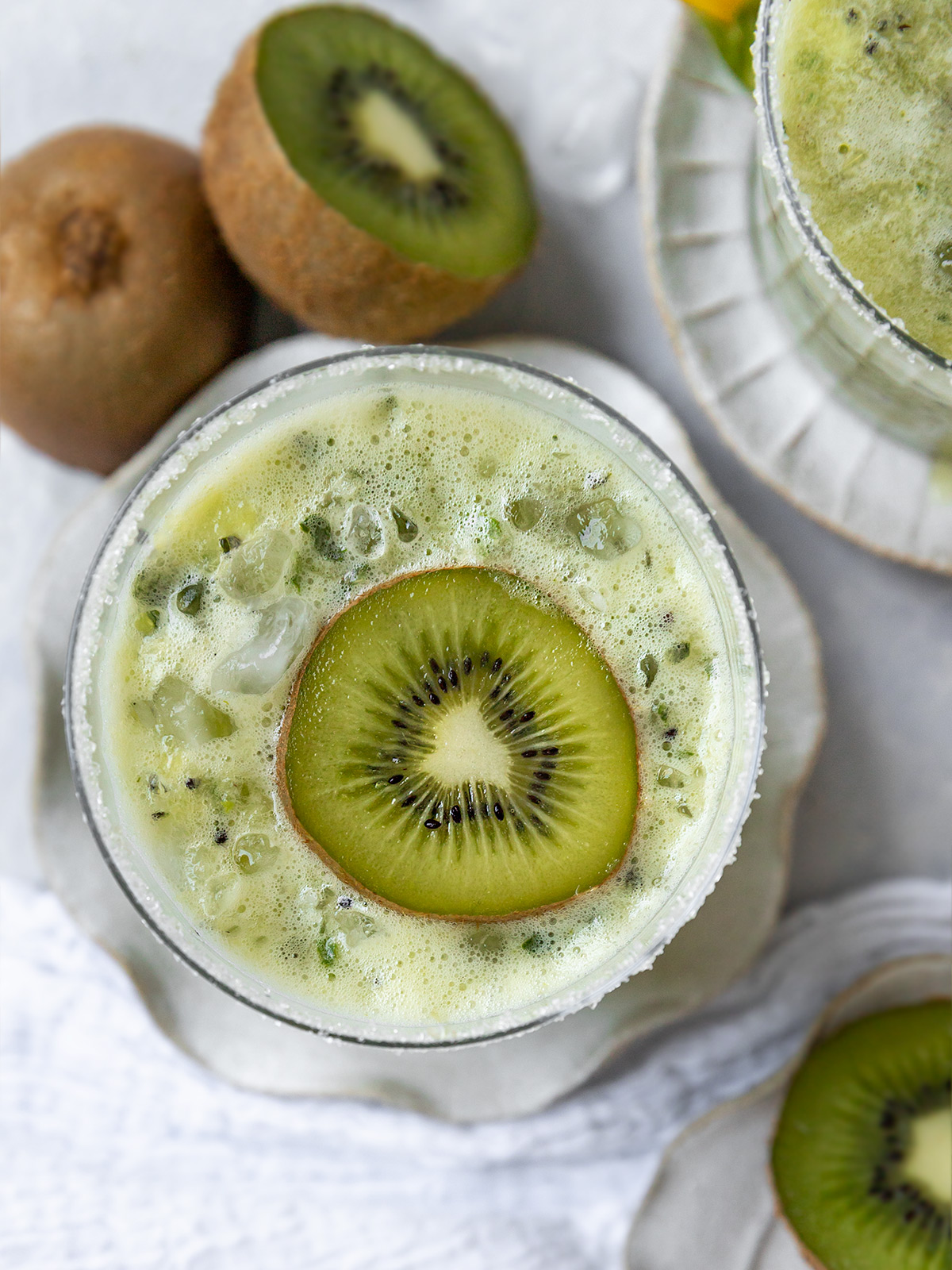 overhead shot of a green margarita topped with a kiwi slice