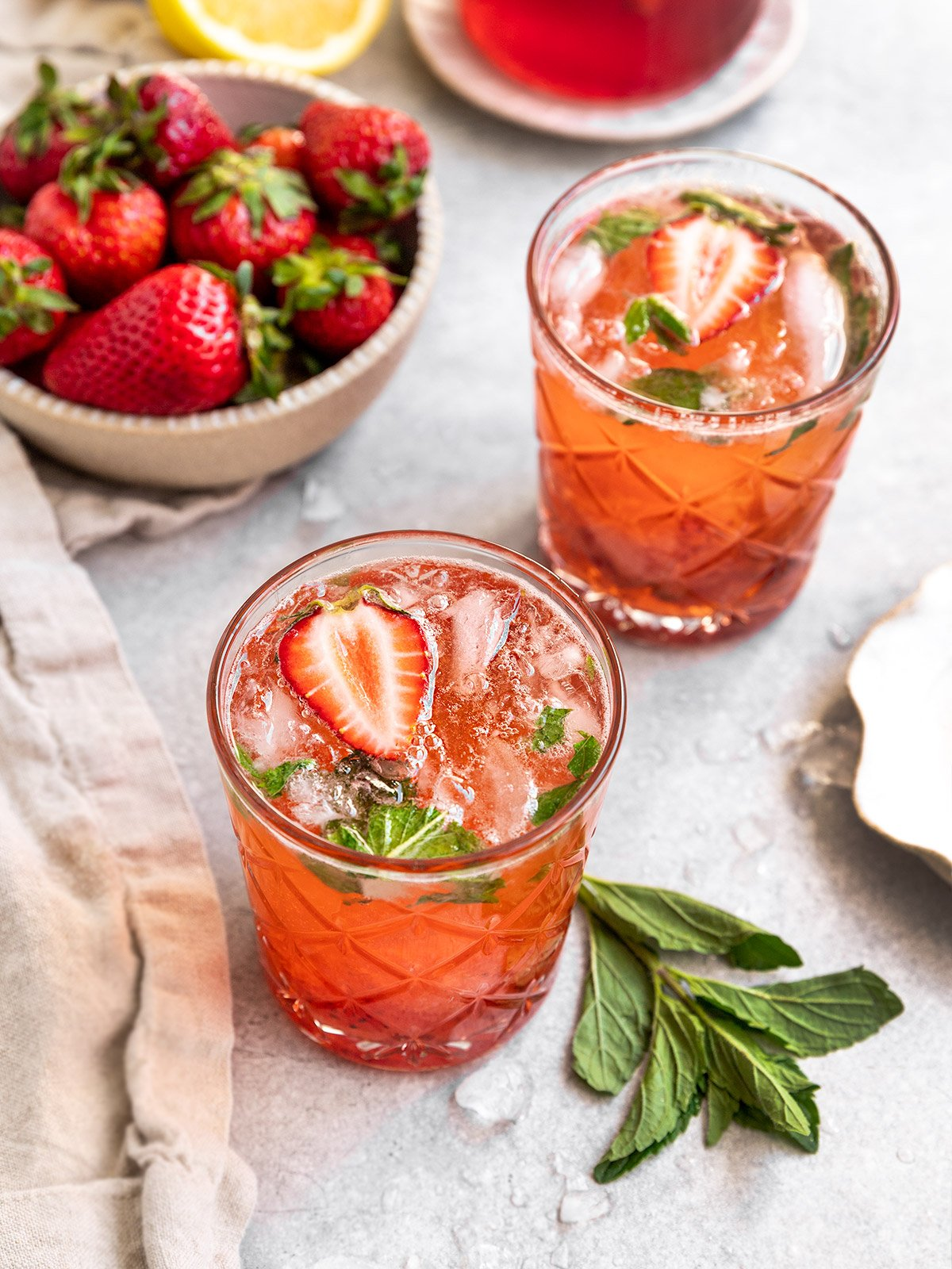 two mojitos with strawberrise and mint alongside a bowl of strawberries