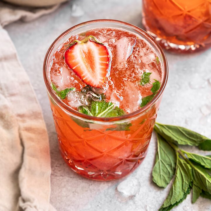 a strawberry mint mojito with a slice of strawberry on top