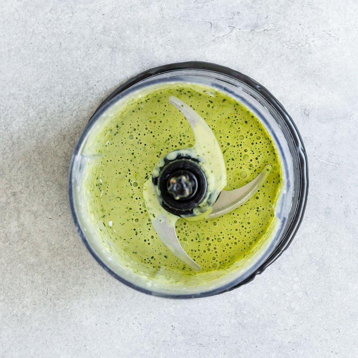 a food processor full of a green lemon cilantro tahini sauce