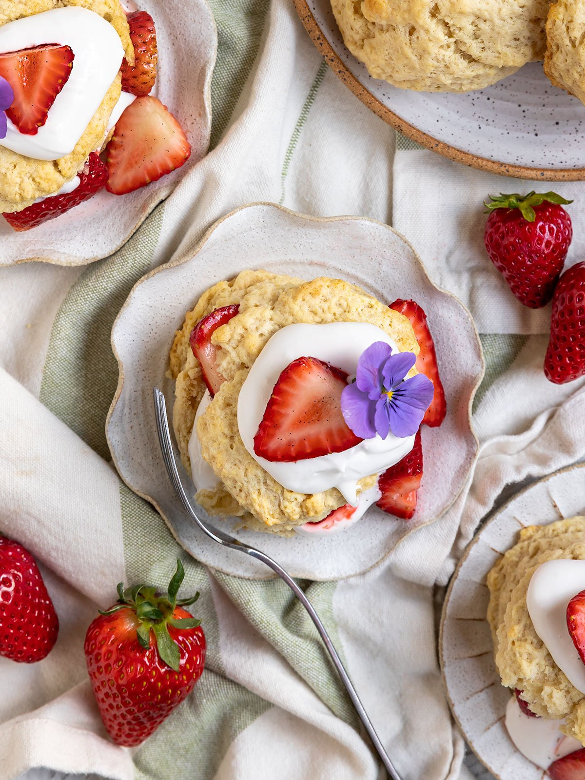 three plates topped with biscuits with strawberries and coconut cream on top