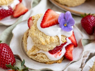 plate with a biscuit filled with layers of coconut cream, vanilla strawberries, and a flower on top