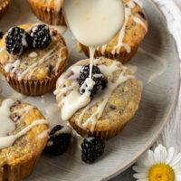 spoon drizzling lemon glaze onto a plate of blackberry muffins