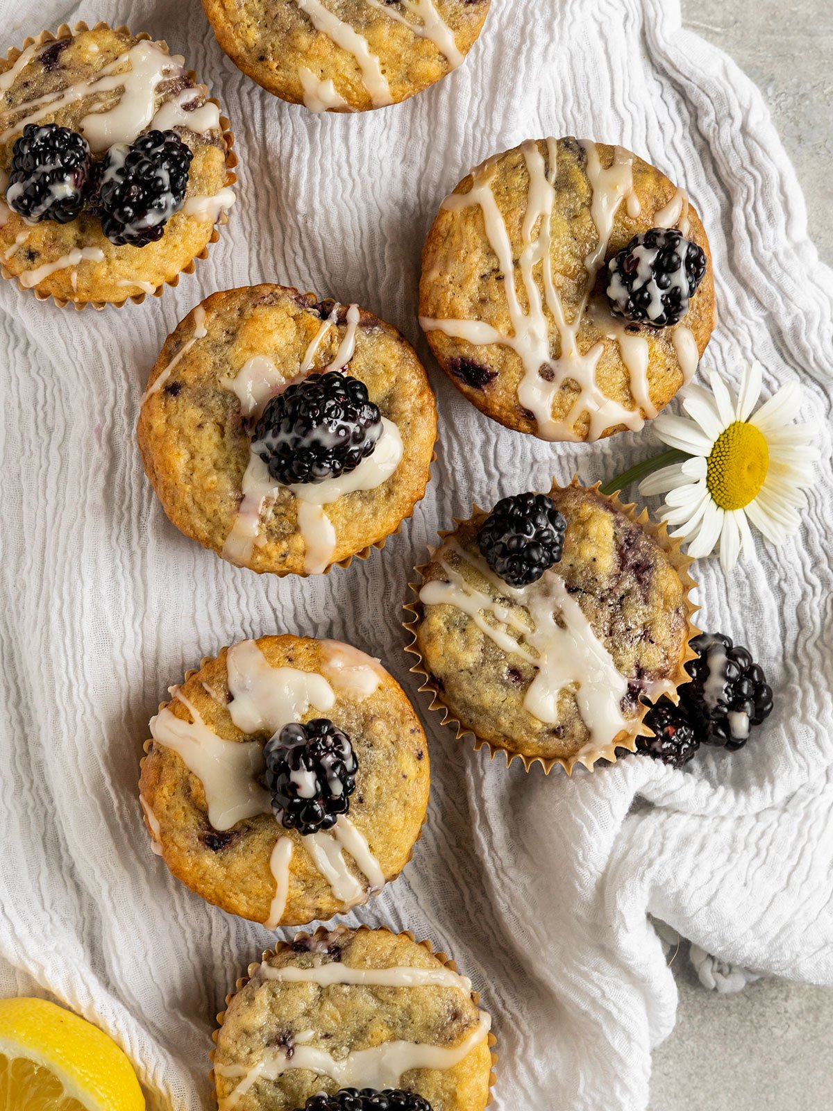 overhead shot of blackberry lemon muffins on a linen cloth topped with glaze and fresh blackberries