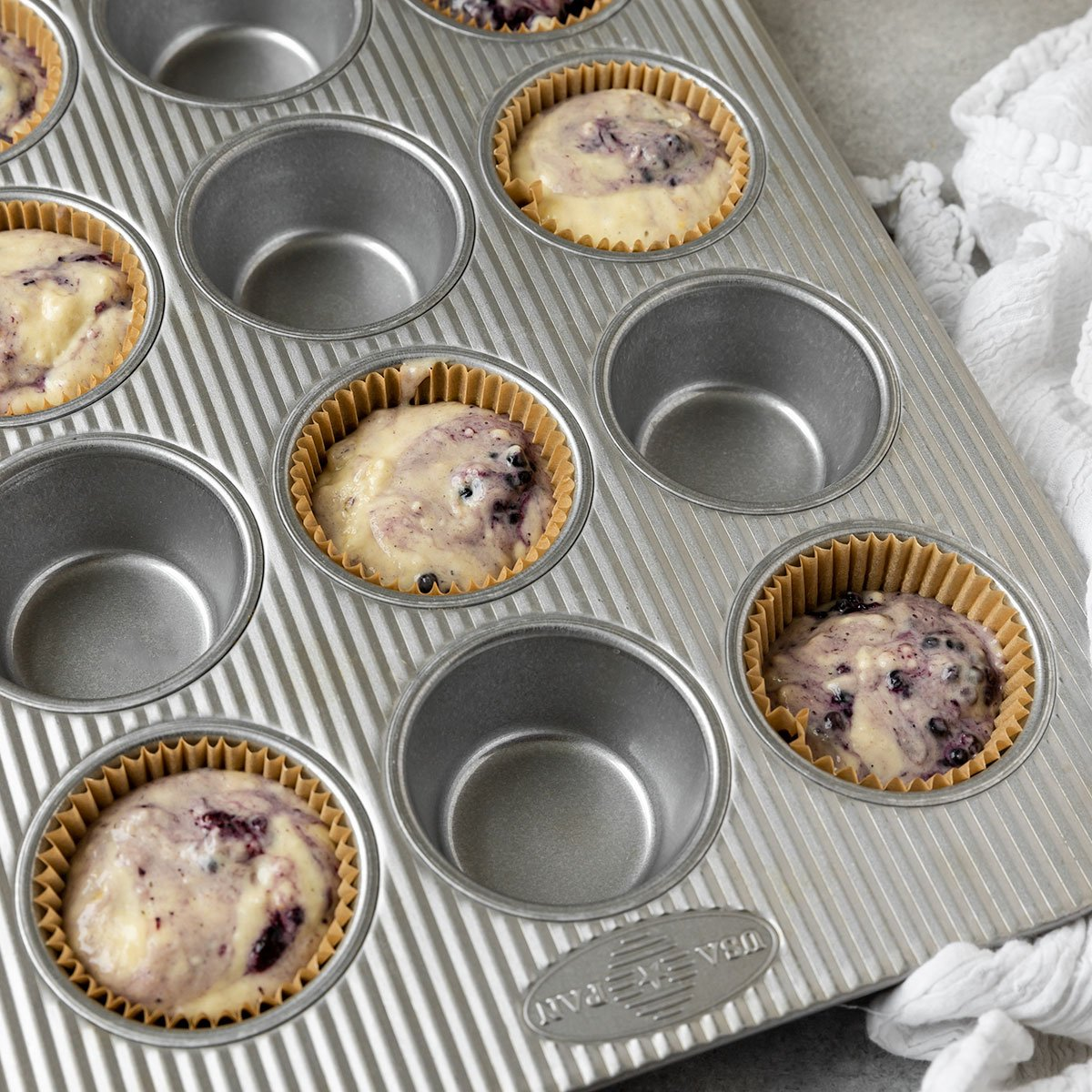 muffin tin filled with 8 cupcake liners full of blackberry lemon muffin batter before baking