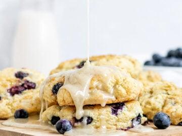 glaze being poured onto blueberry scones