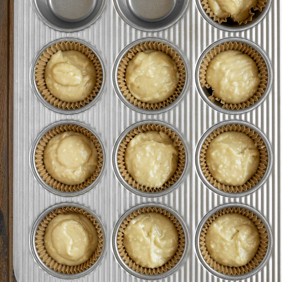 10 cupcake liners in muffin tin filled with coconut cupcake battre