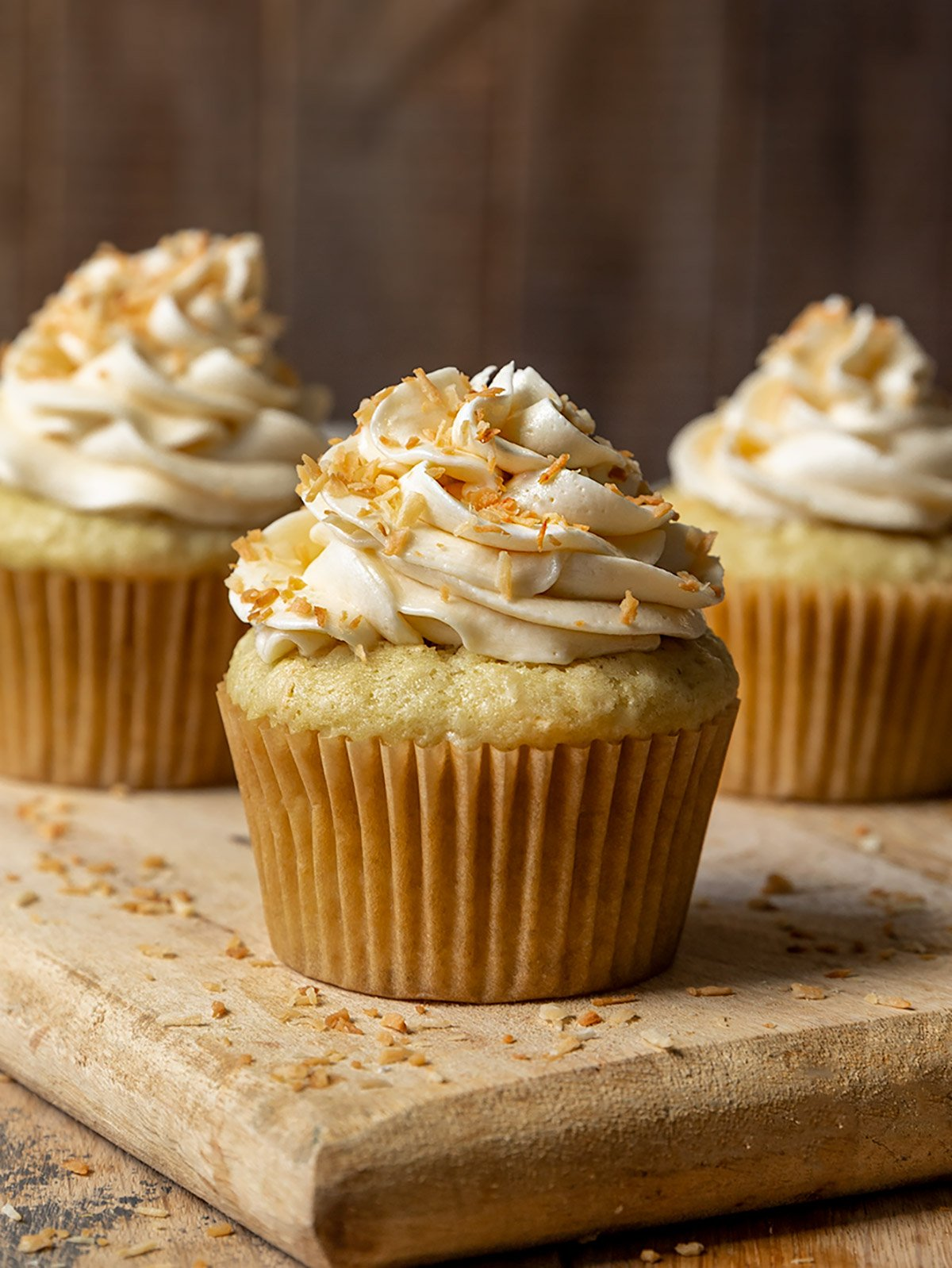 a close up shot of three coconut cupcakes with frosting and toasted coconut on top