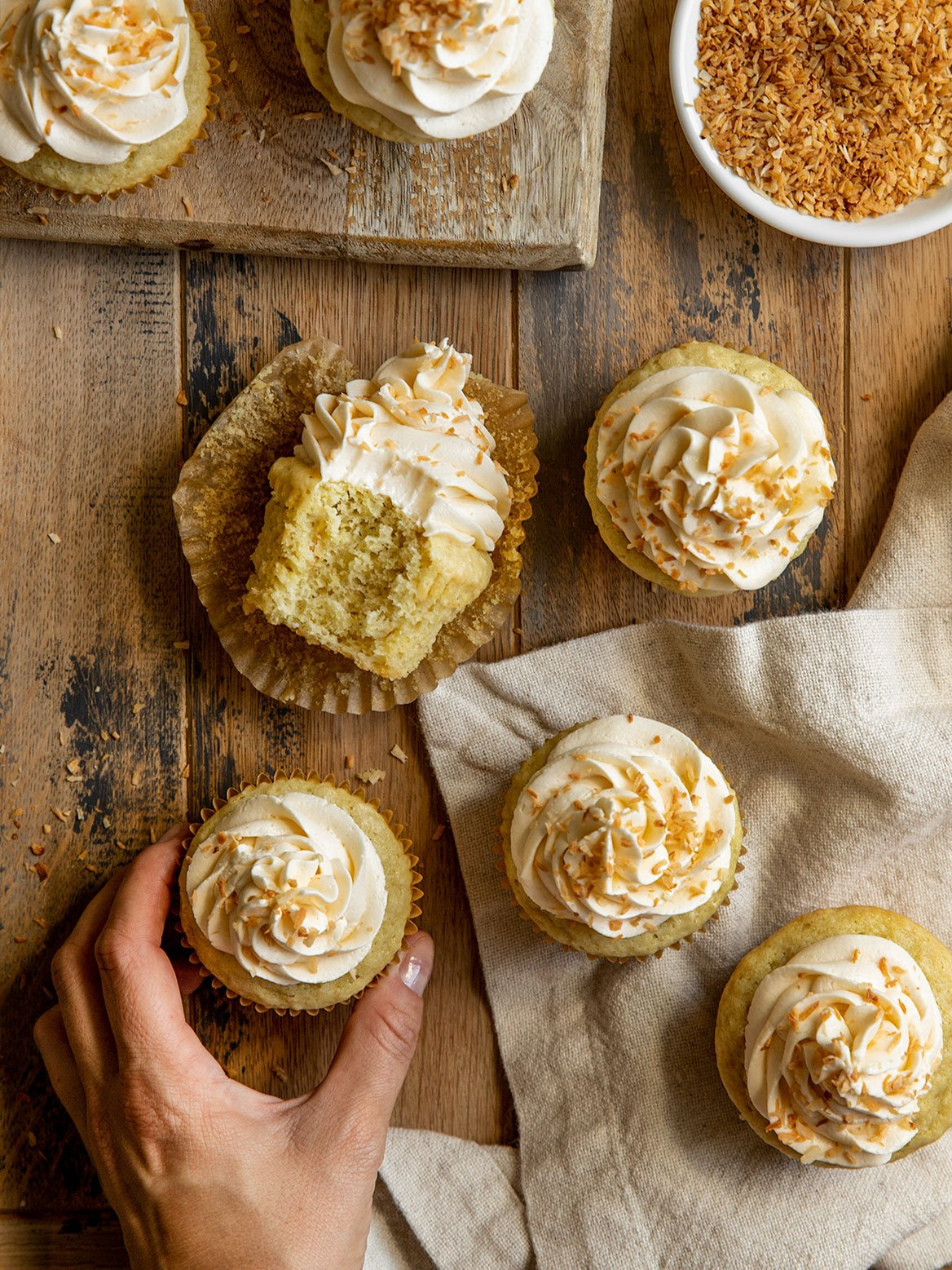 hand reaching for a coconut cupcake