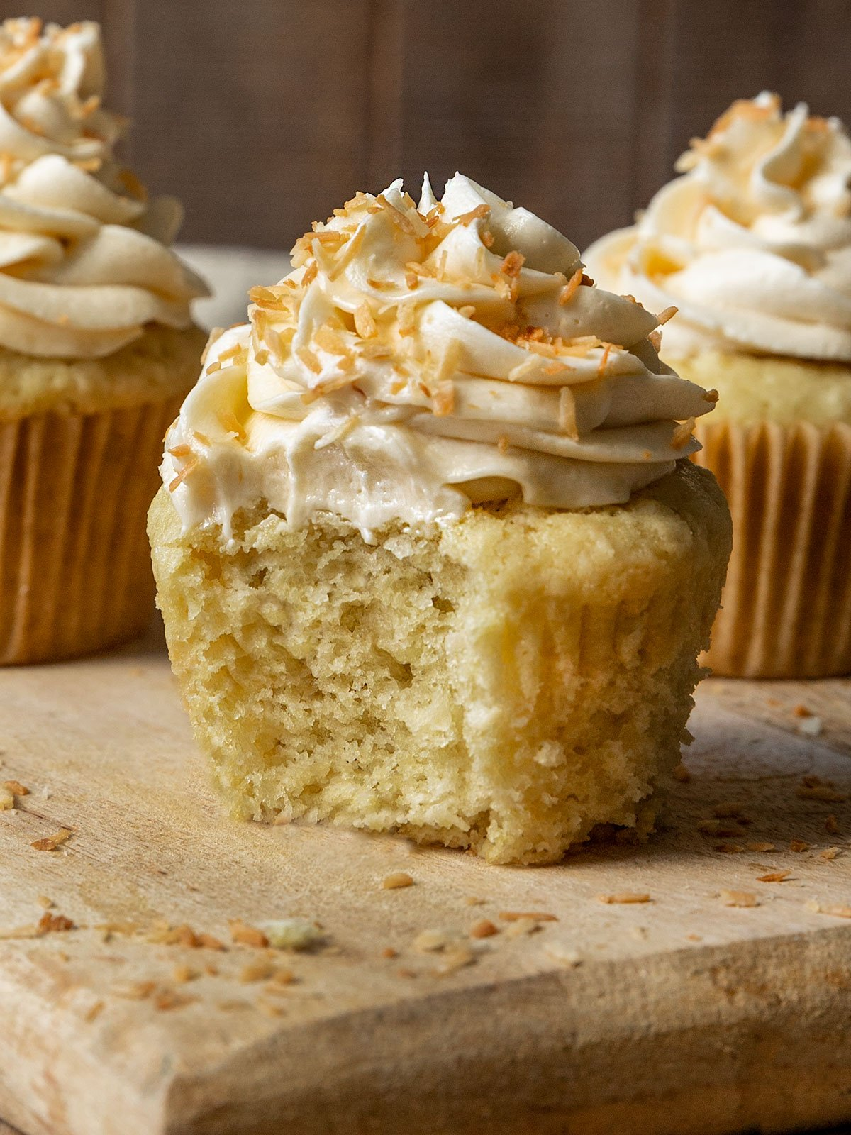 coconut cupcake with a bite taken out to show fluffy texture inside