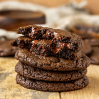 pile of double chocolate chip cookies with top cookie broken in half to show fudgy center and melty chocolate chips