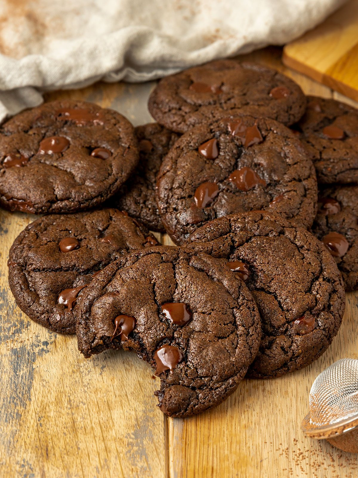 pile of chocolate chocolate chip cookies with one missing a bite to show fudgy texture inside