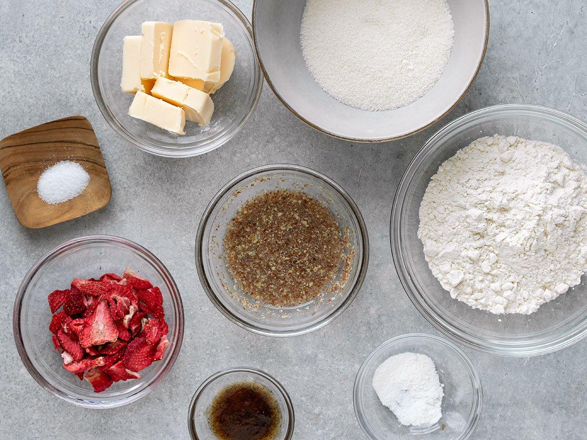 overhead shot of ingredients including vegan butter, sugar, dried strawberries, flax egg, flour, baking powder, baking soda, vanilla, and salt
