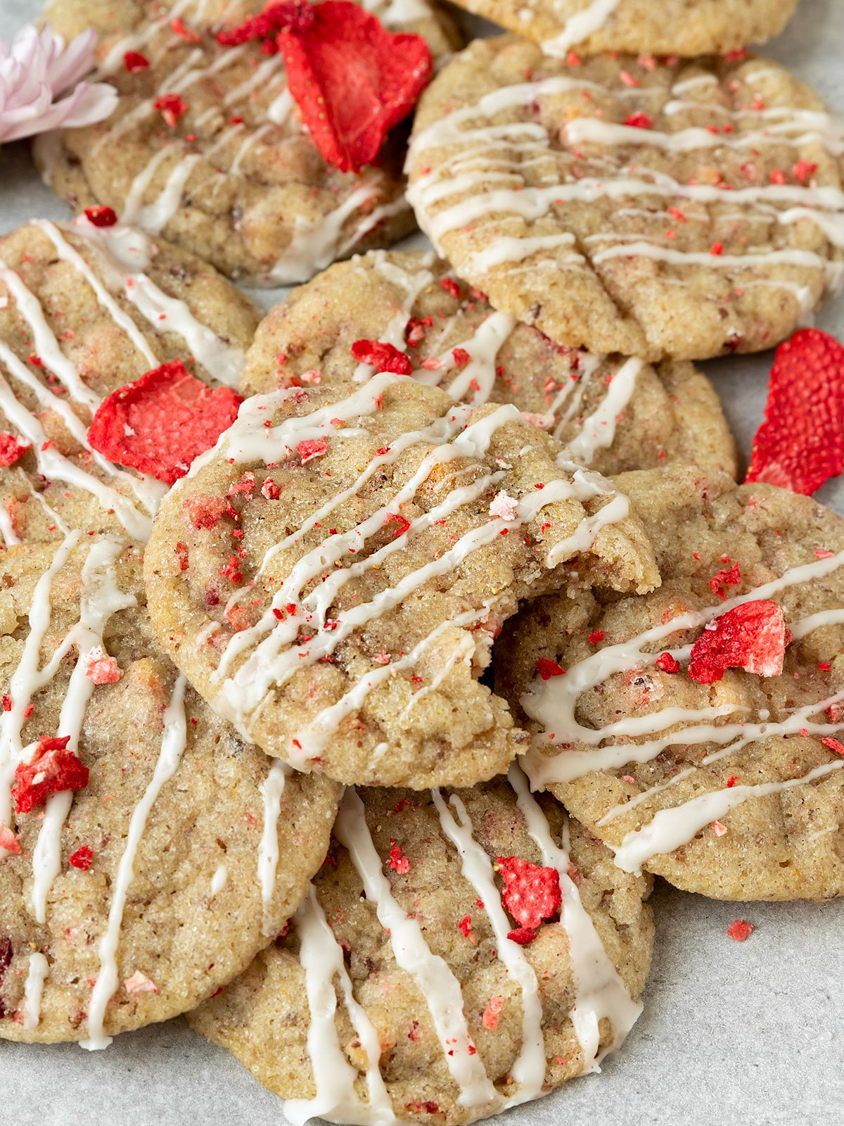 pile of strawberry cookies with vanilla glaze and dried strawberries with top cookie missing a bite