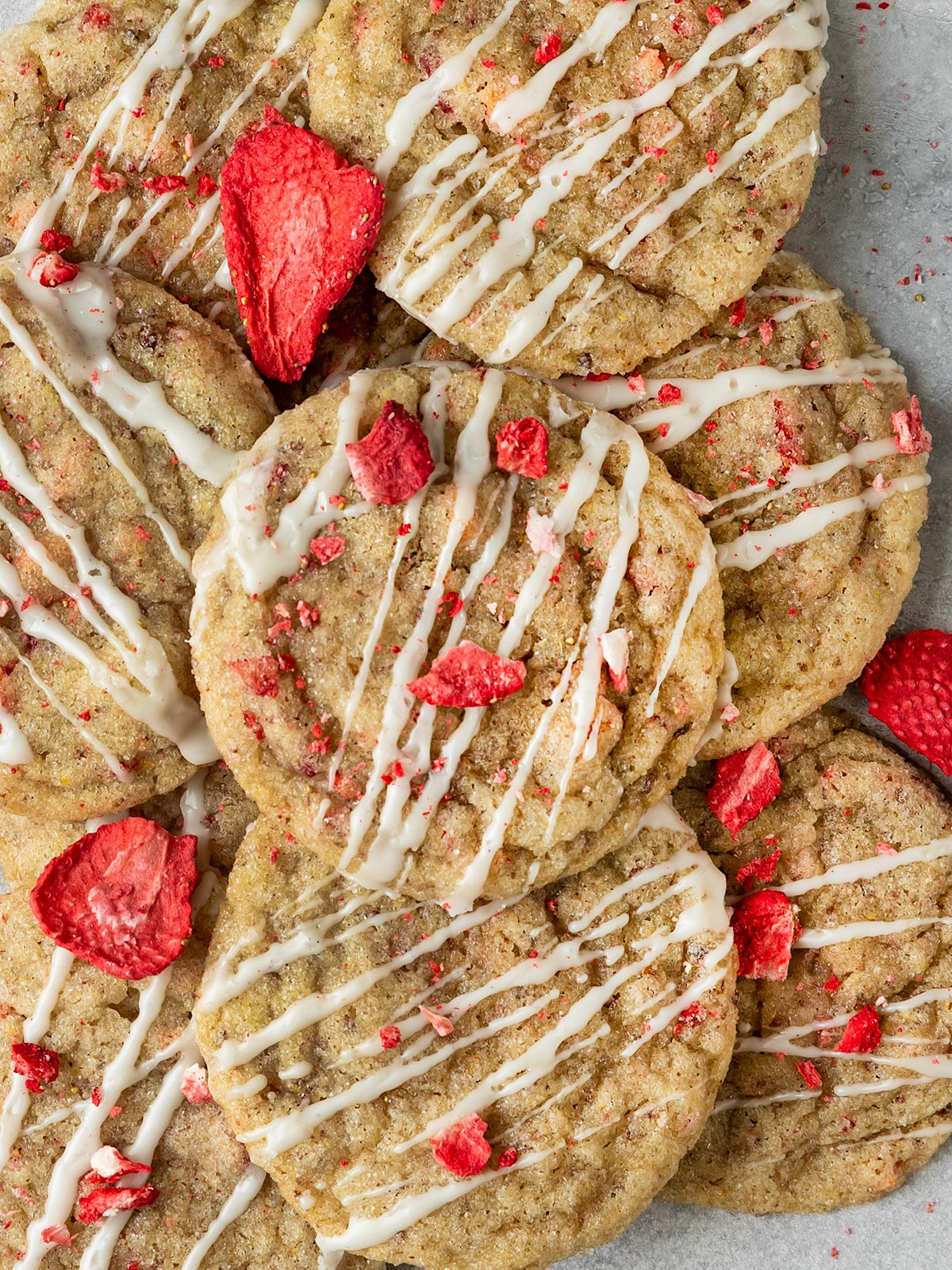 pile of cookies topped with vanilla icing and dried strawberry pieces
