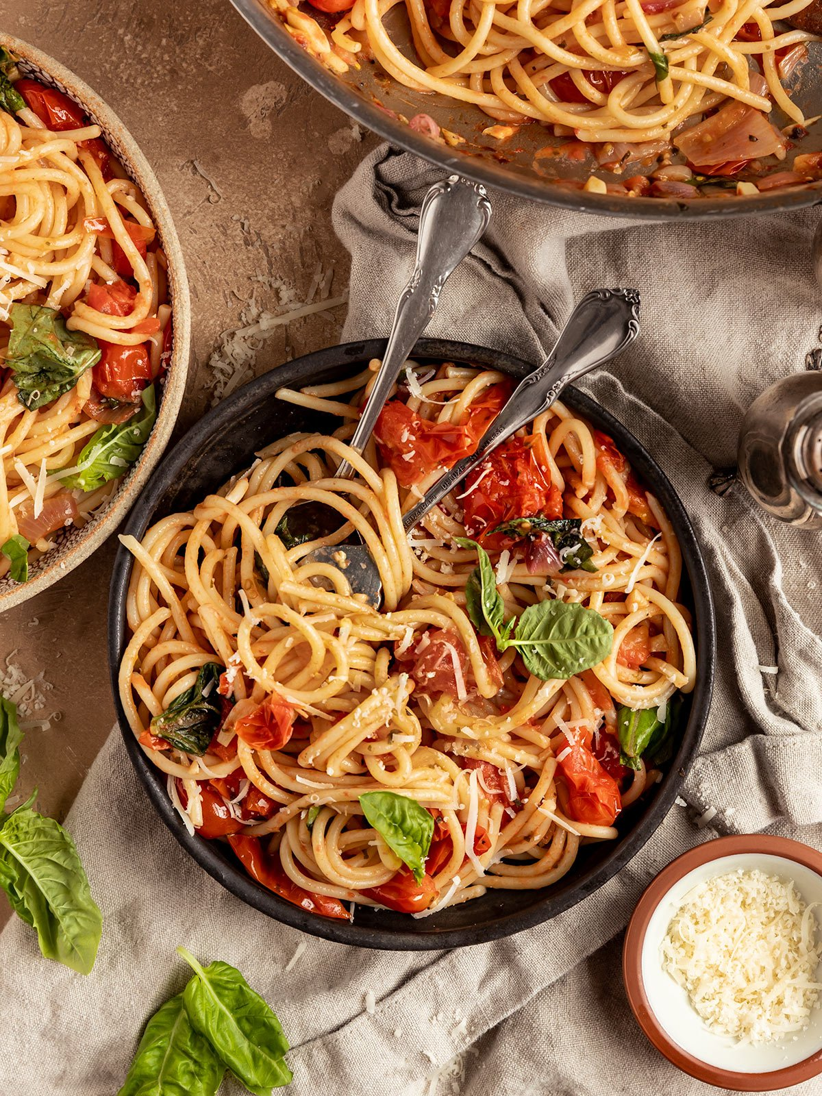 overhead shot of three bowls of pasta with cherry tomatoes, basil, and vegan parmesan