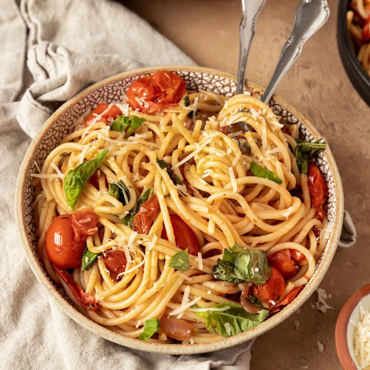 bowl of pasta with burst cherry tomatoes, basil, vegan parmesan, and two forks