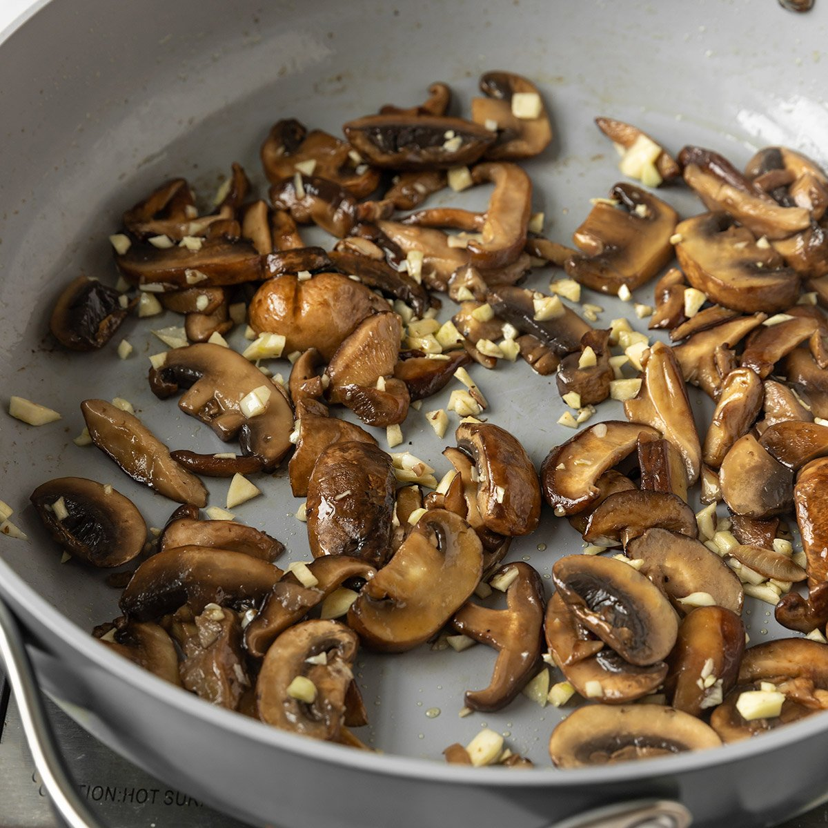 mushrooms and garlic being cooked in a saute pan