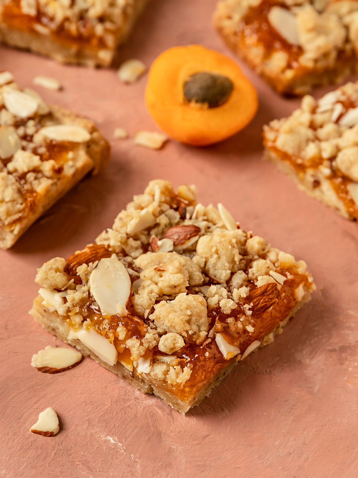 close up shot of apricot bar with a thick apricot jam layer and almond crumble topping