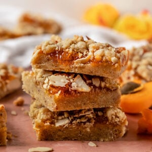 three crumble bars filled with apricot jam stacked on top of eachother