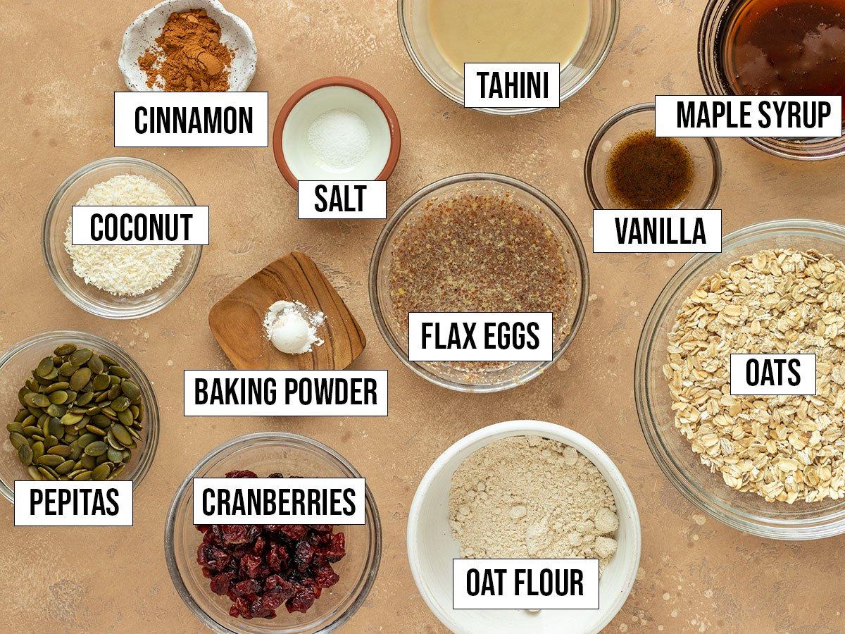 labeled ingredients including oats, oat flour, pepitas, coconut, cranberries, vanilla, tahini, cinnamon, baking powder, salt, maple syrup