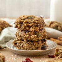 stack of three cookies on a plate filled with cranberries, pepitas, coconut, and oats