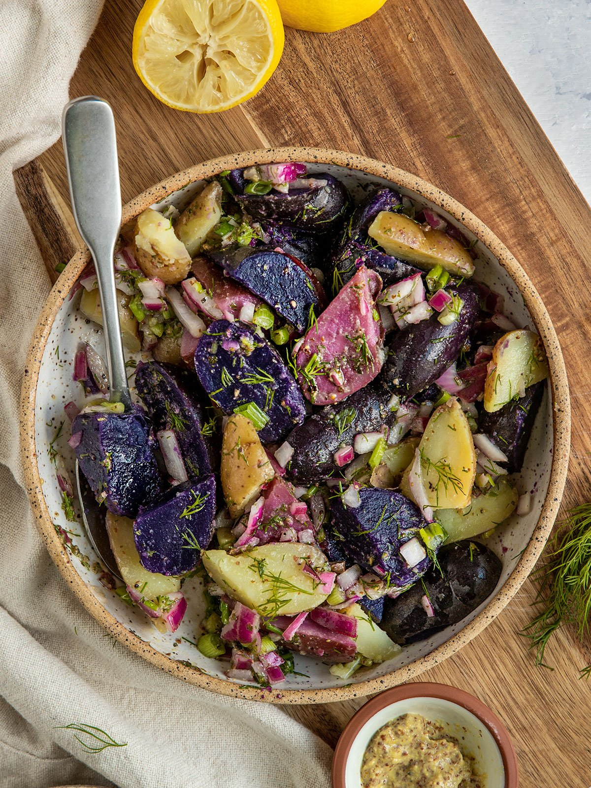 a bowl of potato salad with fingerling potatoes, dill, scallions, red onion, and a dressing