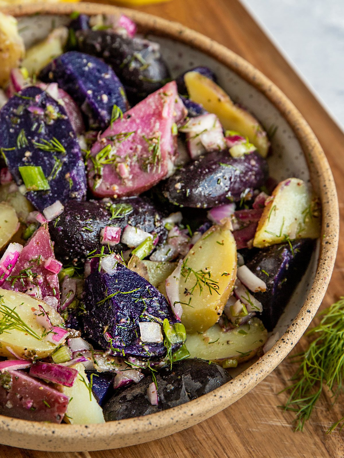 pink, purple, and white fingerling potato salad with dill, scallions, and onion in a bowl