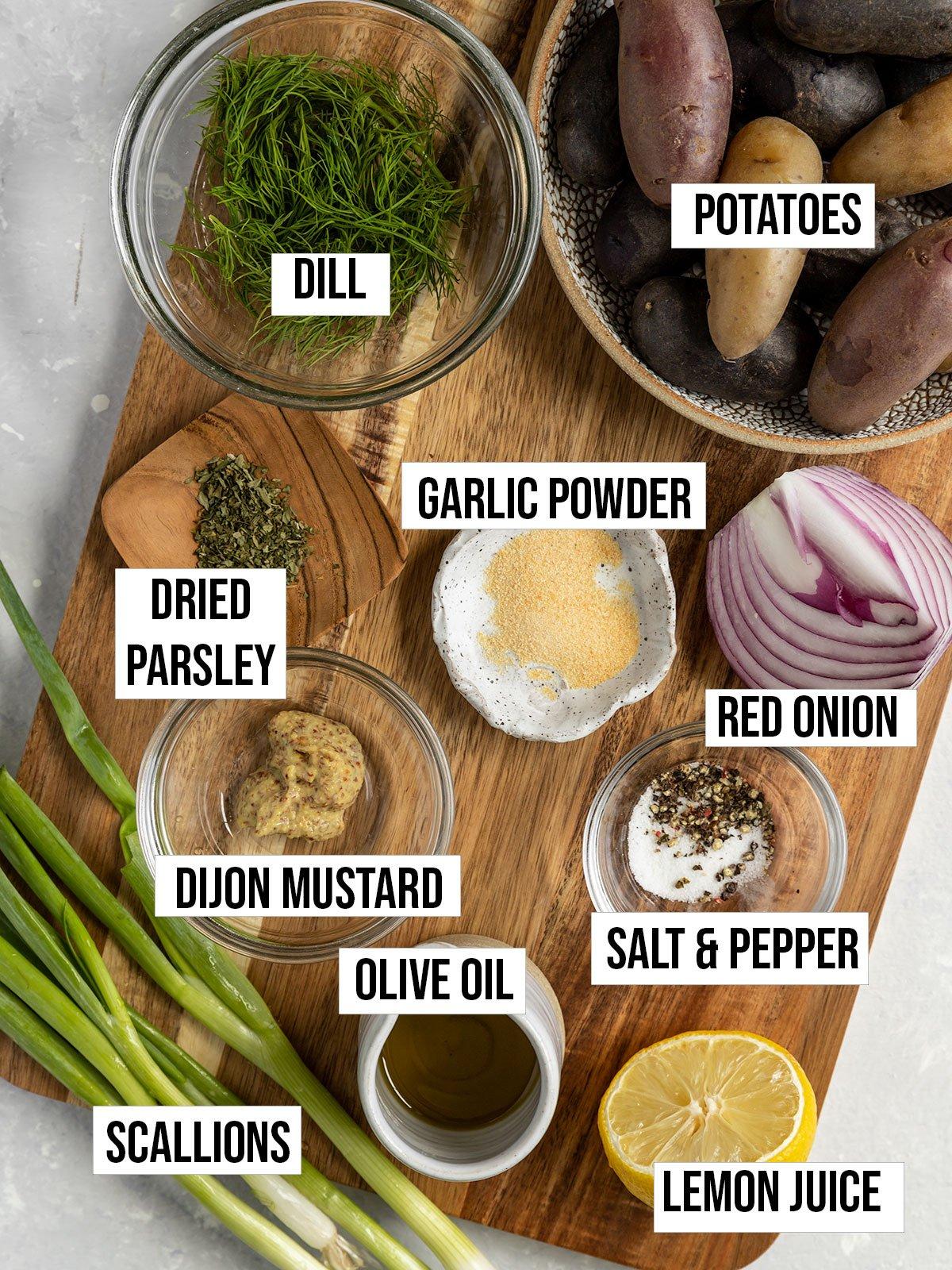 labeled ingredient shot with dill, potatoes, onion, garlic powder, lemon, salt, pepper, olive oil, scallions, and mustard