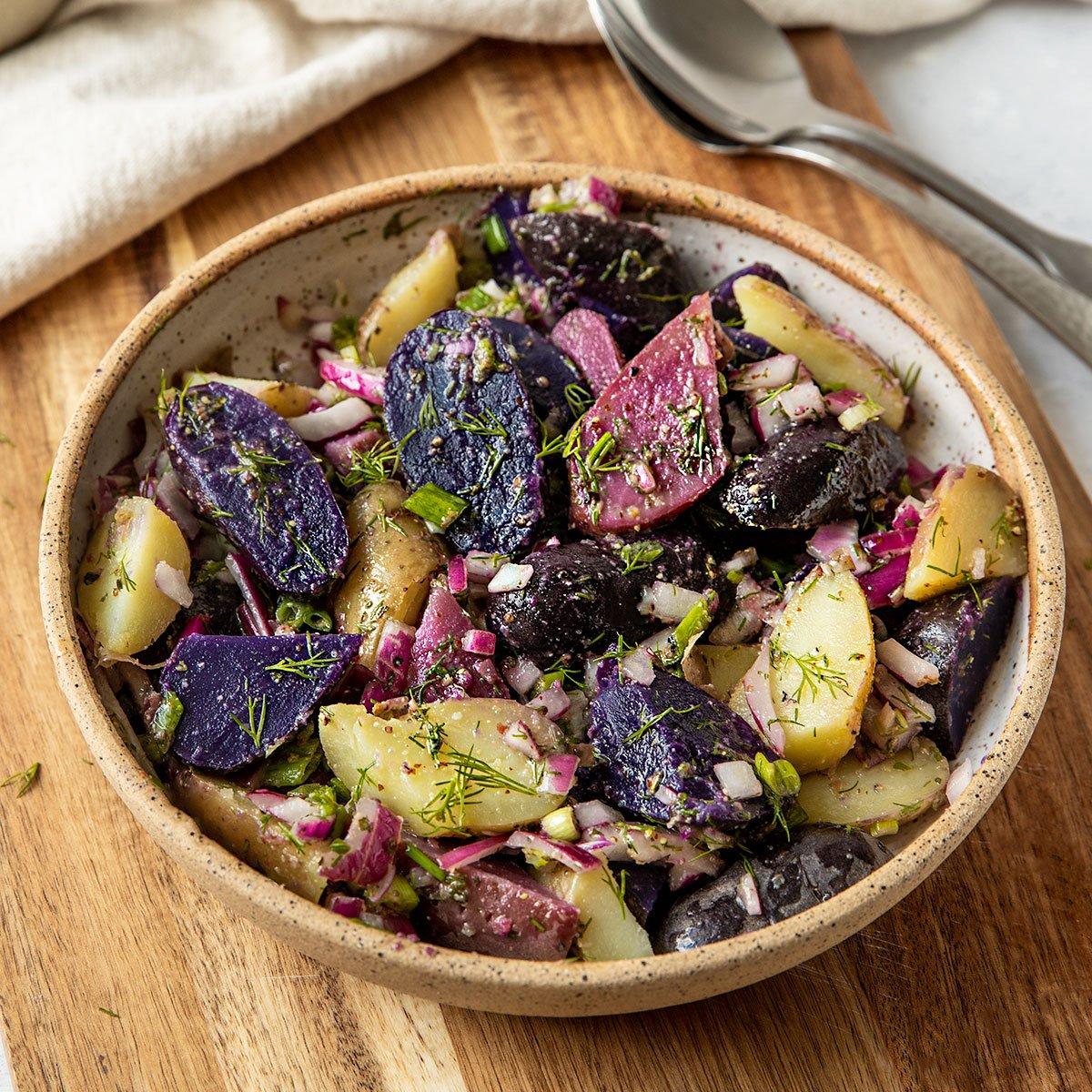 a bowl of purple, pink, and white fingerling potatoes with a dill dressing