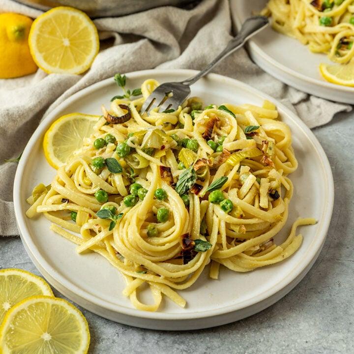 plate of lemon pasta with peas, leeks, and fresh oregano on top