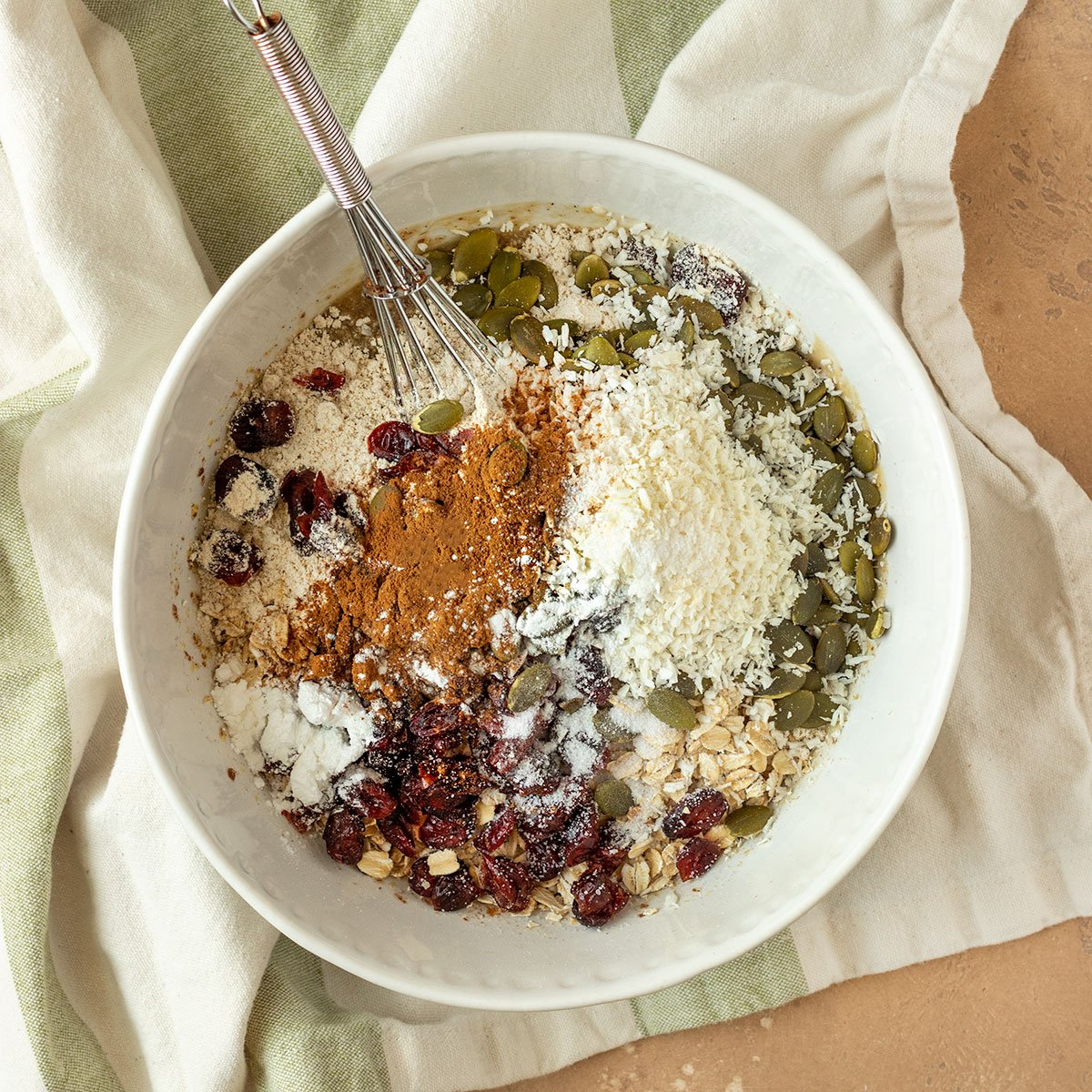 mixing bowl filled with oats, pepitas, cranberries, coconut, cinnamon, baking powder, salt