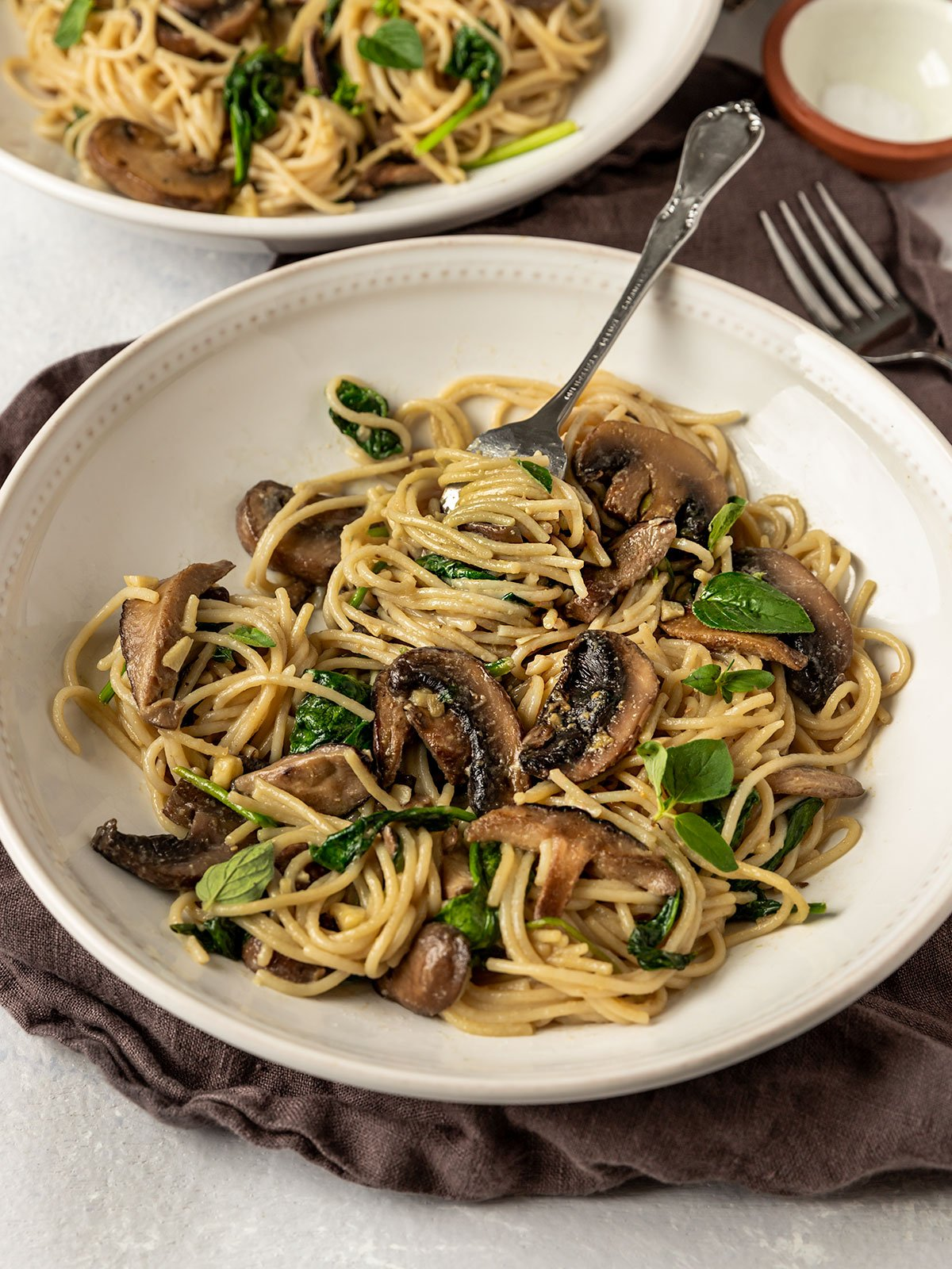 a plate of pasta with mushrooms, spinach, and miso butter sauce